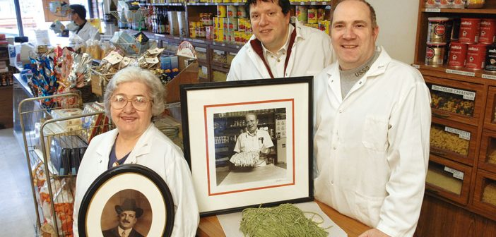 Three generations of Raffettos (from left): Romana holds a portrait of Marcello, who opened the store in 1906, while her sons, Richard and Andrew, stand behind a portrait of their father, Gino. Photo by Leo Sorel