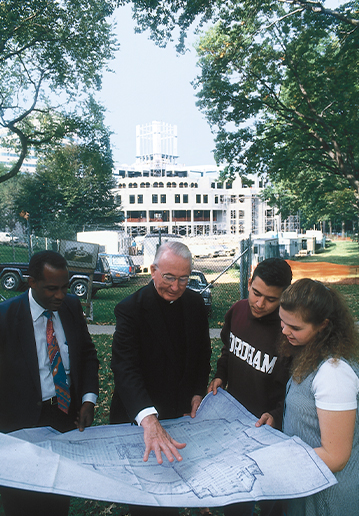 While construction of the new library is under way, Father O'Hare reviews the floor plan with student leaders.
