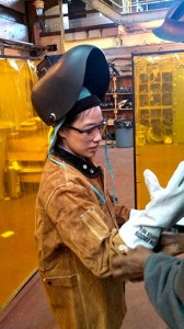 Amy Batallones, FCLC '13, suits up in welding gear to do mechanical work at one of Con Edison's steam-generating stations.