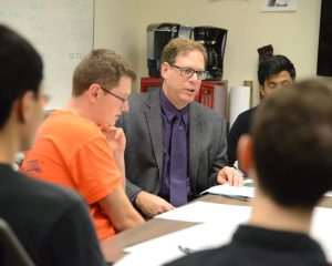 Gary Weiss, director of the Wireless Sensor Data Mining Lab, works with his students to integrate their Actitracker app into smartwatches. (Photo by Joanna Mercuri)