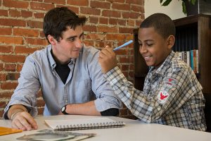 Fordham senior Harrison Pidgeon (left), a volunteer with POTS's Family Club program, helps Rayvon learn long division. (Photo by Bud Glick)