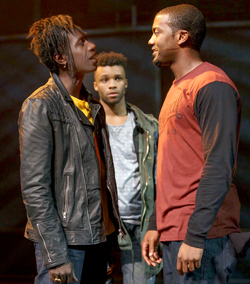 Saul Williams as Joh, Dyllon Burnside as Anthony (background), Joshua Boone as Darius, in Holler If Ya Hear Me. Photo by Joan Marcus