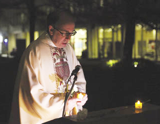 The Rev. John P. McDonagh speaks during the candlelight ceremony on the Lincoln Center campus.  Photo by Bruce Gilbert