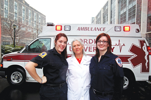 Kathleen Malara, center, advises F.U.E.M.S., which runs ambulances on the Rose Hill campus. Joining are students Amanda Walker, left, and Maeve Bassett, right. Photo by Bruce Gilbert
