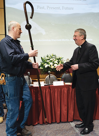 Fordham master carpenter Victor Birone presents the archbishop with a custom-made crosier adorned with Irish symbols and the seal of the Society of Jesus. Photo by Leo Sorel