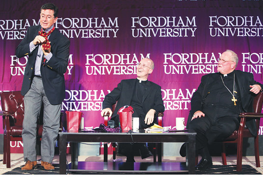 """Masters of Wit and Witness Stephen Colbert, left, dons a Fordham tie after receiving it as a gift from  Joseph M. McShane, S.J., president of Fordham. Colbert appeared with  Timothy Cardinal Dolan, right, and James Martin, S.J., center, in """"The Cardinal  and Colbert: Humor, Joy, and the Spiritual Life"""" on Sept. 14."""