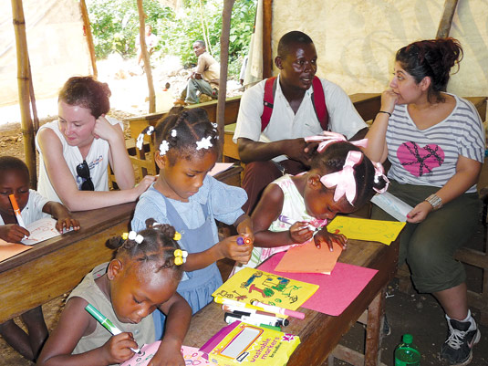 Tania Bailon, GSS '13, left, and GSS student Bridgette Ames, right, with the principal of the Joie D'espoir (Joy of Hope) Primary Community School in Cayes Jacmel, Haiti. Fordham students raised $5,000 to build the foundation for the school's new building.