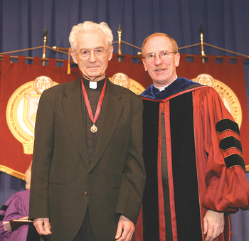 Father Hegyi, left, receives the Bene Merenti medal from Father McShane in 2007. Photo by Michael Dames