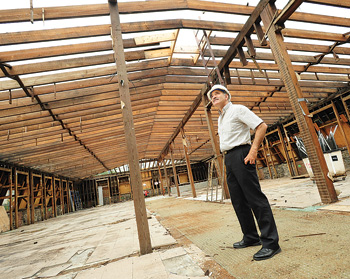 John Spaccarelli gazes skyward through the old roof beams of Hughes Hall.  Photo by Chris Taggart