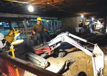 Workers from Tishman Construction operate front loaders deep inside Hughes Hall. Photo by Chris Taggart