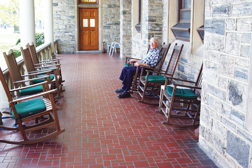 Brother Sebastian Boccabella, S.J., enjoys the expansive porch of Loyola Hall. The Jesuits will give up residence so that the University can expand.  Photo by Nicholas Lombardi, S.J.