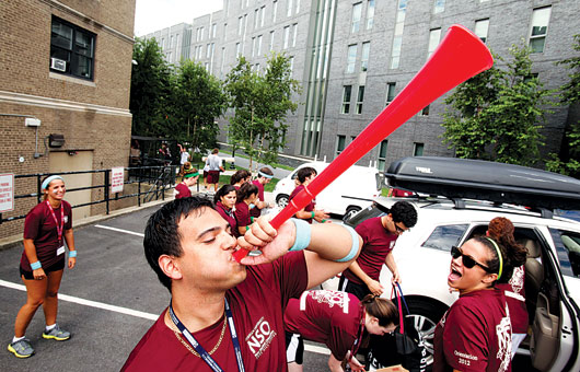 FCRH senior Chris Hernandez, center, was one of the volunteer upperclassmen greeting new Fordham freshmen at Martyrs' Court—with a vuvuzela. The University welcomed some 1,870 students in the new class.  Photo by Bruce Gilbert