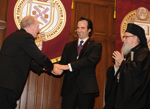 Joseph M. McShane, S.J., president of Fordham (left), and Archbishop Demetrios, primate of the Greek Orthodox Church in America (right), offically install Aristotle Papanikolaou, Ph.D., as the Archbishop Demetrios Chair in Orthodox Theology and Culture. Photo by Chris Taggart