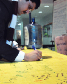 FCRH junior Muhammad Sarwar signed a prayer banner filled with encouraging words. Volunteers bring the 12-foot banners to the sites they visit. Photo by Joanna Klimaski