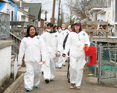 Vicki Gruta, left, worked with a crew removing debris from beaches and properties afflicted by Hurricane Sandy. Photo by Bruce Gilbert