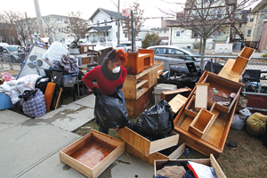Home owner Kendra Newkirk, FCRH '2000, bags personal items lost in Hurricane Sandy, which destroyed the contents of her home in the Rockaways. Photo by Bruce Gilbert