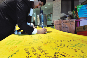 FCRH junior Muhammad Sarwar signs a prayer banner filled with encouraging words. Student, staff, and faculty volunteers bring the 12-foot banners to the sites they visit. Photo by Joanna Klimaski