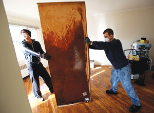 Victor Gunsalus, FCRH '93 and Henry Siccardi, FCRH '12, remove a ruined cabinet from Newkirk's home. Photo by Bruce Gilbert