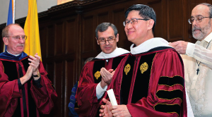Professor Henry Schwalbenberg, right, helps Cardinal Tagle adjust his hood at the honorary degree ceremony. To the left are Father McShane and Edward Stroz, GSB '79, vice chair of Fordham's Board of Trustees. Photo by Bruce Gilbert