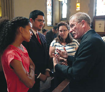 """Joseph M. McShane, S.J., president of Fordham, speaks with junior Ashley Davis before the March 22 Call to Unity service. """"We are a community that welcomes,"""" Father McShane said in his sermon. Photo by Bruce Gilbert"""