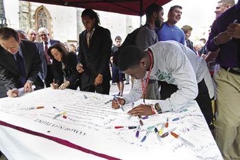 Rose Hill campus student Sam Ajala, a member of the Fordham football team, signs the community pledge against acts of hatred and bias following the Unity service. Photo by Bruce Gilbert