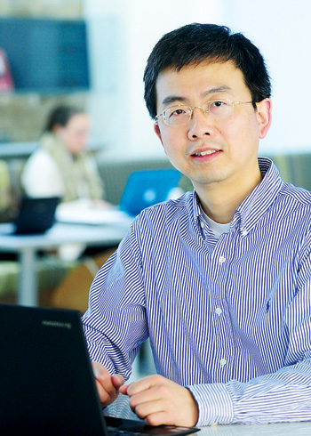 Honggang Zhang, Ph.D., examines computer networks online for issues of safety, reliability and efficiency. Photo by Chris Taggart