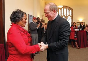 """Joseph M. McShane, S.J., president of Fordham, congratulates Georgia Edwards of Custodial Services, who """"shows up for work every day, early, ready and proud.""""  Photo by Bruce Gilbert"""