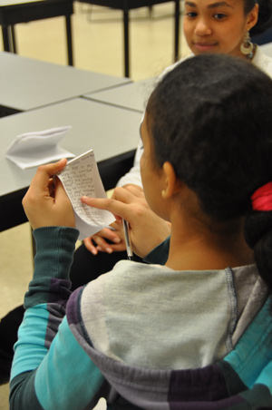 A program participant checks over her notes after interviewing Dahiana Lessard, a bookkeeper with HPAC who also served in the U.S. Army. Photo by Gina Vergel.