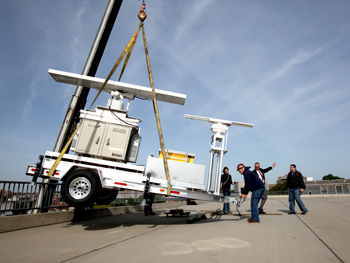 A crane hoists the 4,000-pound avian radar unit onto the top of the Fordham parking garage. Photo by Bruce Gilbert