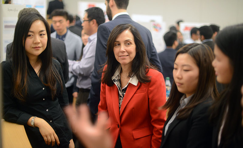 Donna Rapaccioli, dean of the Gabelli School of Business, listens to student presenters.