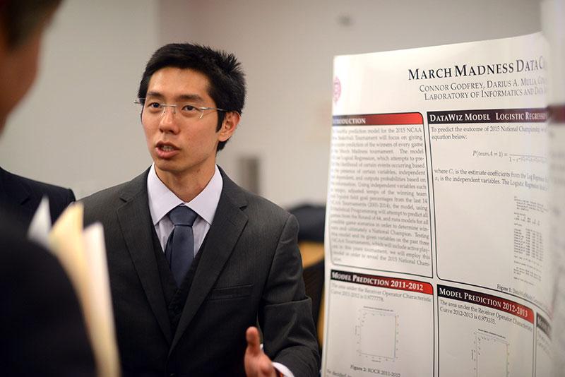 Darius Mulia, of Team Data Whiz, presents the group's logistic regression model to the judges.