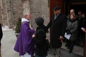 Father McShane greets worshipers outside the Rose Hill Church after mass.