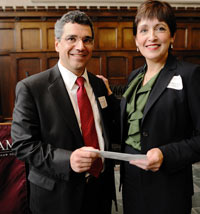 Leonard Cali (FCRH '82), senior vice president for AT&T, delivers a check to Cathleen Lane, director of corporate relations for Fordham.