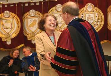 Casimira Stricker, a 40-year employee, is congratulated by Joseph M. McShane, S.J., president of Fordham. Photo by Bruce Gilbert
