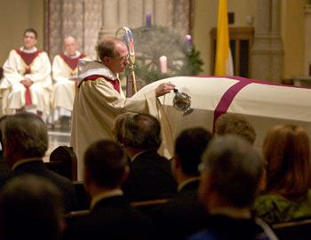 Joseph M. McShane, S.J., president of Fordham, blesses the coffin of Avery Cardinal Dulles, S.J., at the University Church.