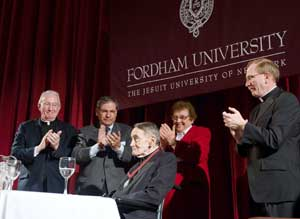 Former Fordham president Joseph A. O'Hare, S.J., John N. Tognino, chairman of the Fordham Board of Trustees, Sister Anne-Marie Kirmse, OP, and Joseph M. McShane, S.J., president of Fordham, lead the applause for Avery Cardinal Dulles, S.J. Photo by Ryan Brenizer