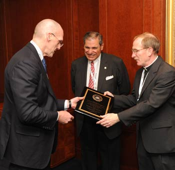 Joseph M. Demarest of the FBI presents a plaque to Joseph M. McShane, S.J., president of Fordham. Demarest also thanked John Tognino (FCLS '75), chair of the Fordham Board of Trustees, for his assistance. Photo by Chris Taggart