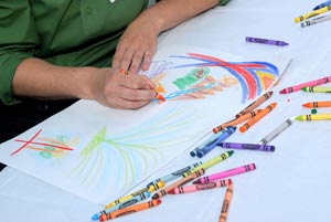 A guest at the conference makes a drawing that represents her life story. Photo by Ken Levinson