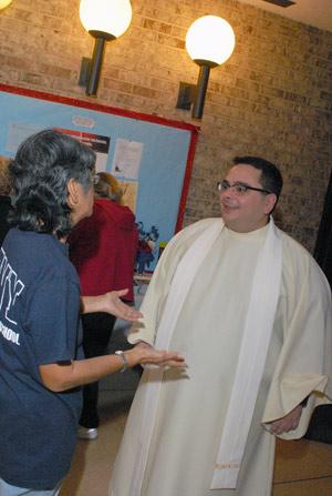 Father Burgaleta speaks with a parishioner at St. Jane Frances de Chantal after Mass.  Photo by Ken Levinson
