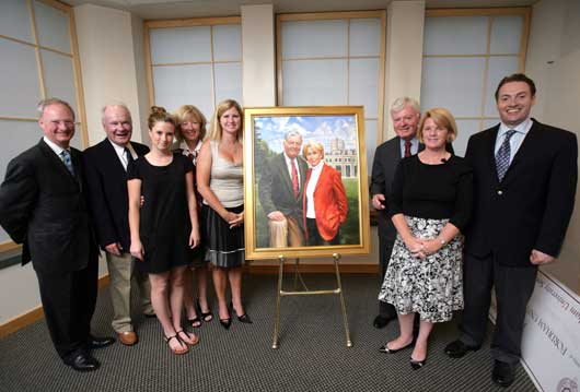 The Walsh Family poses alongside the portrait of William D. Walsh (FCRH '51) and his late wife, Jane, at the President's Club cocktail reception. Photo by Bruce Gilbert