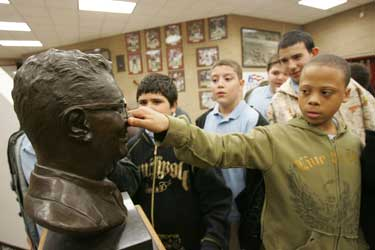 A student from the Urban Institute of Mathematics tweaks the nose on a bust of coaching legend Vince Lombardi at the Lombardi Memorial Center.  Photo by Bruce Gilbert