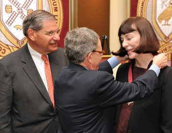 Stephen Freedman, Ph.D., senior vice president for academic affairs/chief academic officer, presents Jo Anna Isaak, Ph.D., with a medal signifying her chair. John Tognino (FCLS '75), chairman of the Fordham University Board of Trustees, was master of ceremonies at the event.  Photo by Chris Taggart