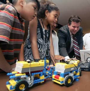 MS 45 students Luis and Brianne watch Kraig DeMatteis (right), technical and curriculum developer for Fordham RETC, set up robotics software. Photo by Bruce Gilbert