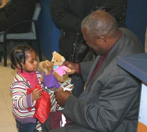 Head Men's Basketball Coach Dereck Whittenburg delivers presents to a child at St. Barnabas Hospital's pediatric clinic.  Photo courtesy of Fordham Athletics