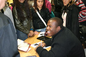 Defensive lineman Thomas Lloyd III signs copies of the book about his life for Bronx high school students. Photo courtesy of Fordham Athletics