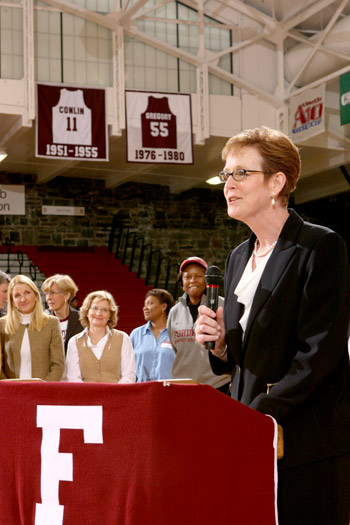 Anne Gregory O'Connell (FCRH '80) speaks to the crowd at halftime of the women's basketball game on Dec. 5 as her retired jersey number hangs in the background. Photo courtesy of Fordham Athletics