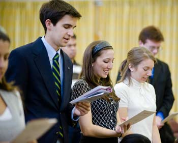 Student inductees recite the Alpha Sigma Nu pledge. Photo by Ryan Brenizer