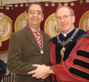 MJoseph M. McShane, S.J., president of Fordham, congratulates Joseph Caputo on receiving the Archbishop Hughes Medal. Photo by Chris Taggart