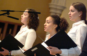 Fordham students Jayne Deeley, Amber Hurst-Martin, and Jessica DiGiovanni, play the chorus in the dramatic performance of Father Berrigan's poem. Photo by Chris Taggart