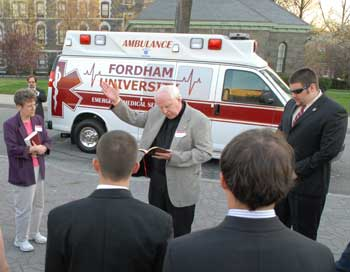 Joseph Currie, S.J., director of campus ministry, leads a prayer before christening FUEMS' new ambulance.  Photo by Chris Taggart